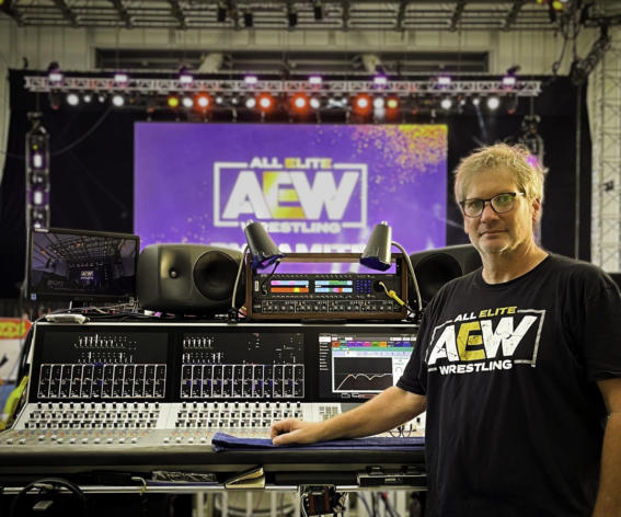 Ryan Glick, FOH Mixer next to a Summa audio mixing console at All Elite Wrestling